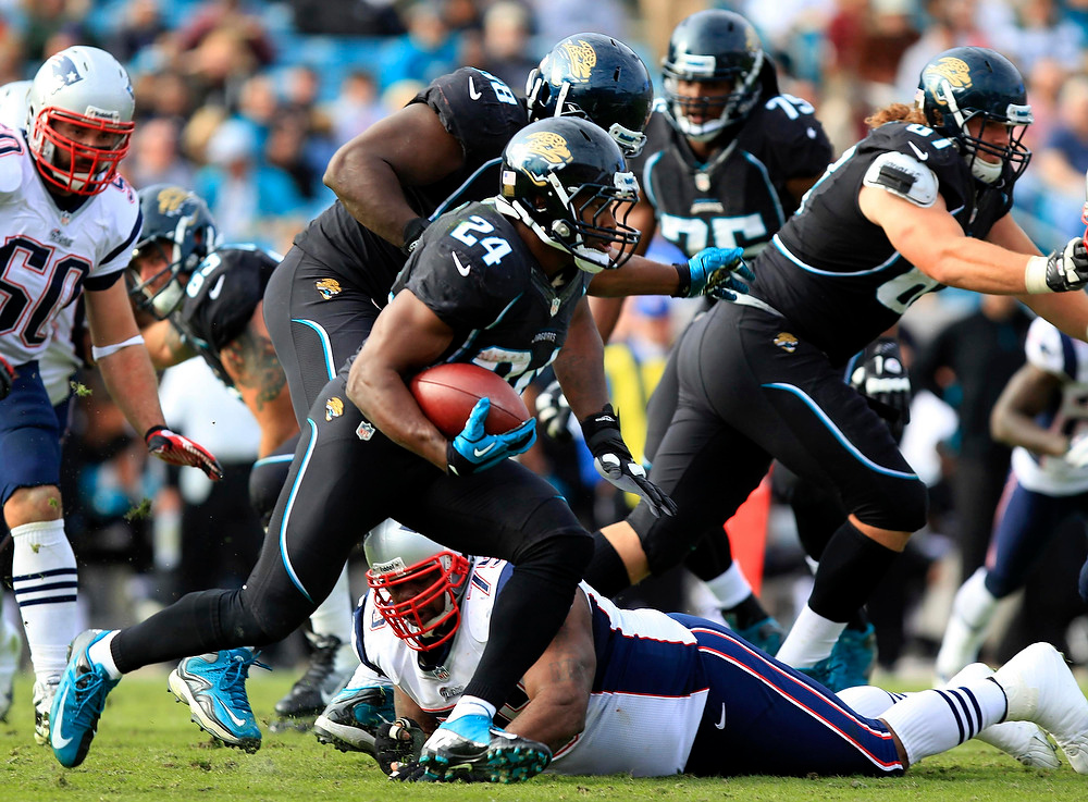 . Jacksonville Jaguars running back Montell Owens (C) runs the ball past the New England Patriots defense during the second half of their NFL football game in Jacksonville, Florida December 23, 2012. REUTERS/Daron Dean