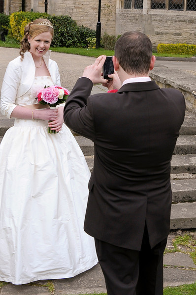 Groom taking Brides photo on his iPhone