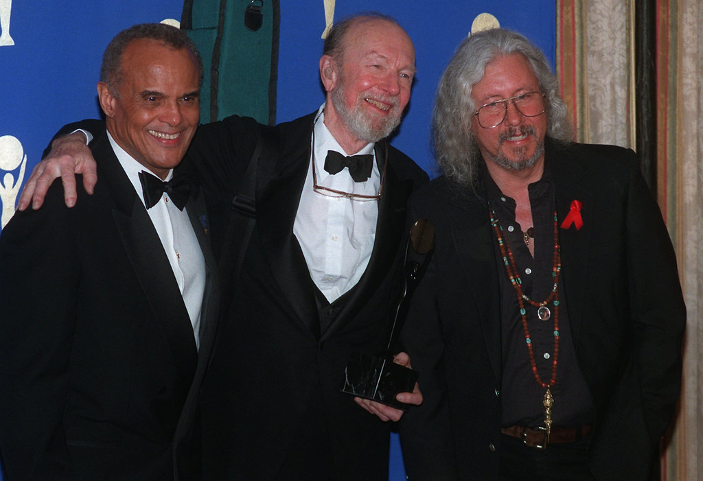 . Folk legend Pete Seeger, center, with his banjo strapped to his shoulder, poses with Harry Belafonte, left, and longtime friend Arlo Guthrie backstage after Seeger\'s induction into the  Rock and Roll Hall of Fame at New York s Waldorf-Astoria Hotel Wednesday, Jan. 17, 1996. Seeger was honored for his early influence on rock performers. (AP Photo/Joe Tabacca)