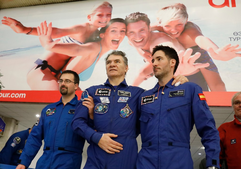 . Italian astronaut Paolo Nespoli, center, is assisted by ESA space agency specialists pose for a photo at the airport of Karaganda, Kazakhstan, Thursday, Dec. 14, 2017. Three astronauts on Thursday landed back on Earth after nearly six months aboard the International Space Station. (AP Photo/Dmitri Lovetsky, Pool)