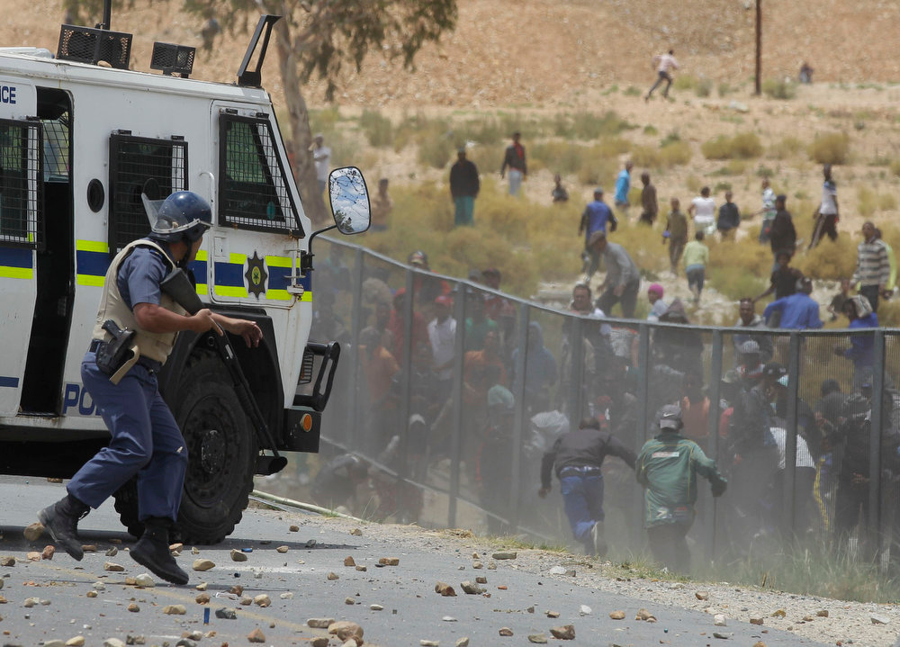 Description of . A South African Police looks on at farm workers throwing rocks at him as they demonstrate in De Doorns , South Africa, Thursday, Jan 10, 2013. Striking farm workers in South Africa have clashed with police for a second day during protests for higher wages. The South African Press Association says police on Thursday fired rubber bullets at rock-throwing demonstrators in the town of De Doorns in Western Cape province, and protests were occurring in at least two other towns. (AP Photo/Schalk van Zuydam)