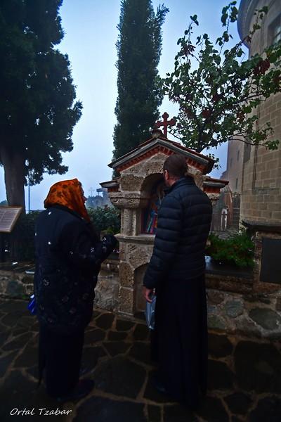 הכומר והמאמינה במנזר במטאורה.jpg