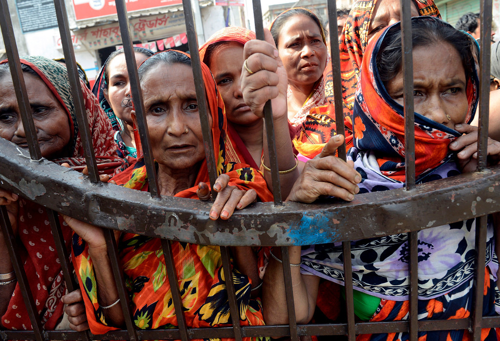 . Women watch from behind a gate while unclaimed bodies are brought to a cemetery from the garment factory building collapse in preparation for a mass burial on Wednesday May 1, 2013 in Dhaka, Bangladesh. (AP Photo/Ismail Ferdous)