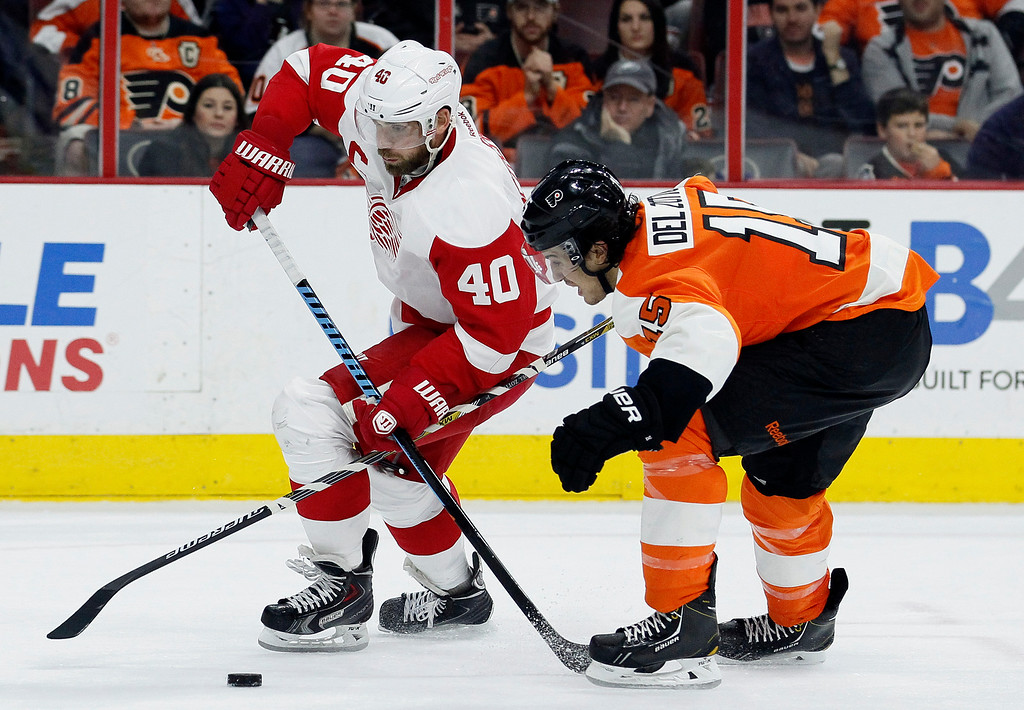 . Detroit Red Wings\' Henrik Zetterberg (40) and Philadelphia Flyers\' Michael Del Zotto, right, cross sticks as Zetterberg brings the puck into the Flyers\' zone in the third period of an NHL hockey game Saturday, Oct. 25, 2014, in Philadelphia. The Flyers won 4-2. (AP Photo/Tom Mihalek)