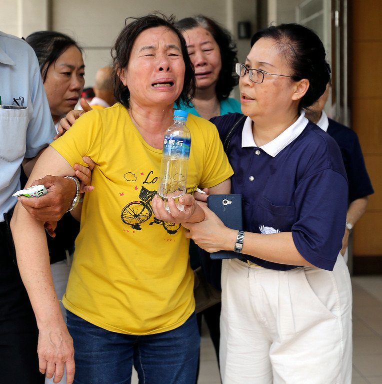 . A relative, left, of a victim in the multiple explosions from an underground gas leak is consoled at a funeral parlor in Kaohsiung, Taiwan, Friday, Aug. 1, 2014. A series of explosions about midnight Thursday and early Friday ripped through Taiwan\'s second-largest city, killing scores of people, Taiwan\'s National Fire Agency said Friday. (AP Photo)