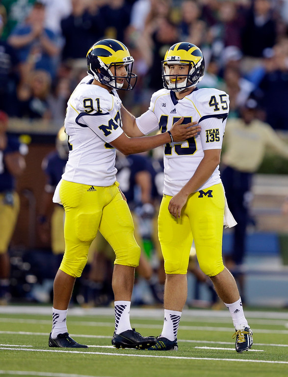. Michigan holder Kenny Allen consoles Matt Wile after Wile missed a field goal against Notre Dame during the first half of an NCAA college football game in South Bend, Ind., Saturday, Sept. 6, 2014. (AP Photo/Michael Conroy)