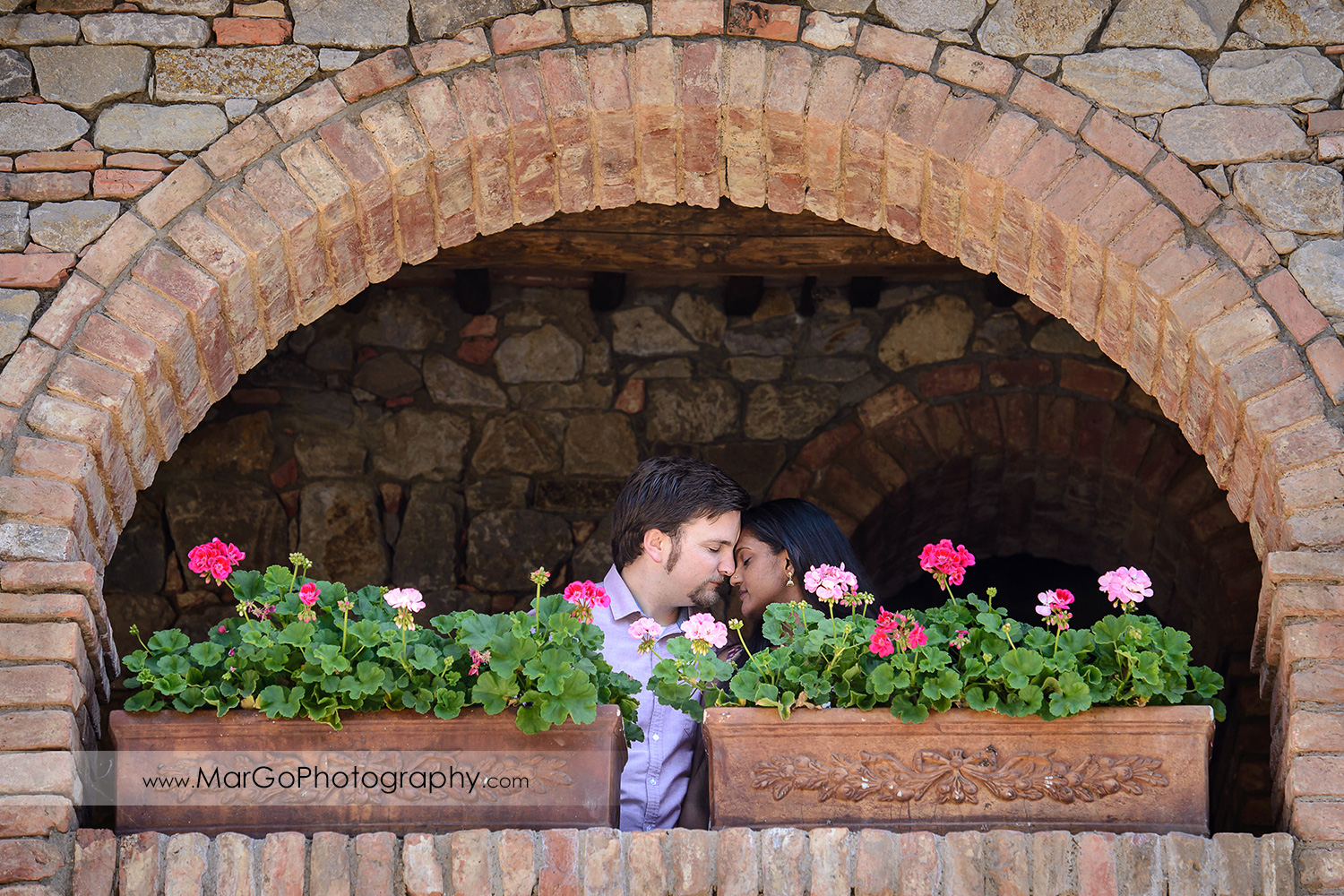 portrait of man in pink shirt and Indian woman in flower dress touching foreheads under brick arch during engagement session at Castello di Amorosa in Calistoga
