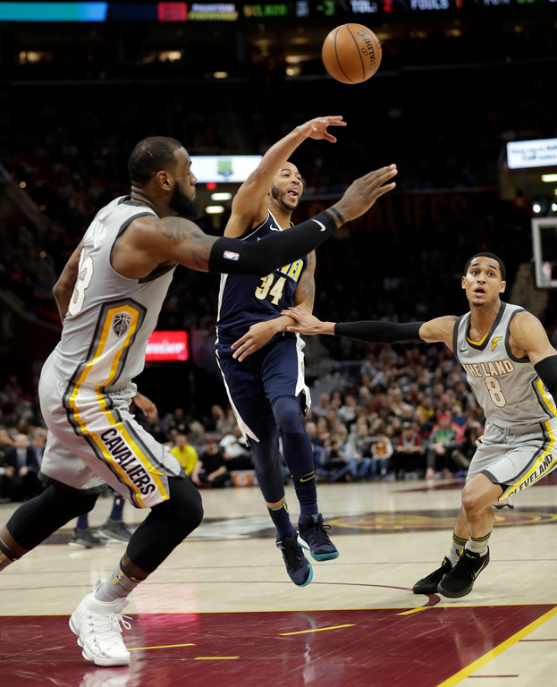 . Denver Nuggets\' Devin Harris (34) passes against Cleveland Cavaliers\' LeBron James (23) and Jordan Clarkson in the second half of an NBA basketball game, Saturday, March 3, 2018, in Cleveland. (AP Photo/Tony Dejak)