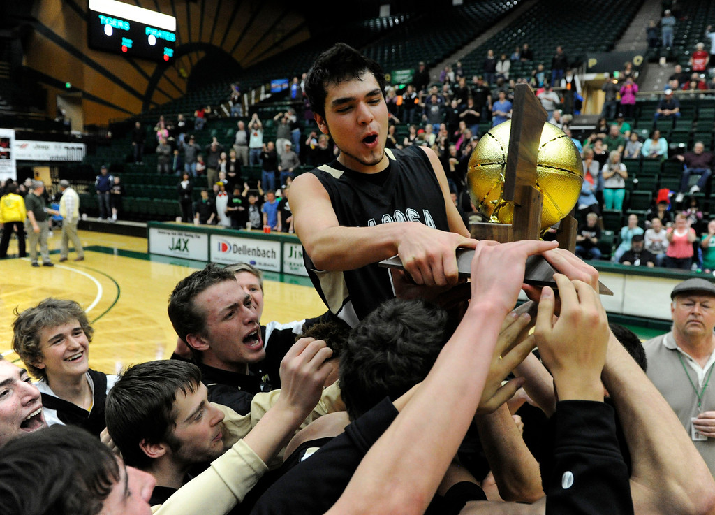 . FT. COLLINS, CO. - MARCH 16TH: Kain Lucero, Pagosa Springs, center, (holding trophy) celebrates with his teammates after defeating Kent Denver 53-49 to win the 3A Boys Colorado State Championship at Moby Arena in Ft. Collins Saturday evening. (Photo By Andy Cross/The Denver Post)