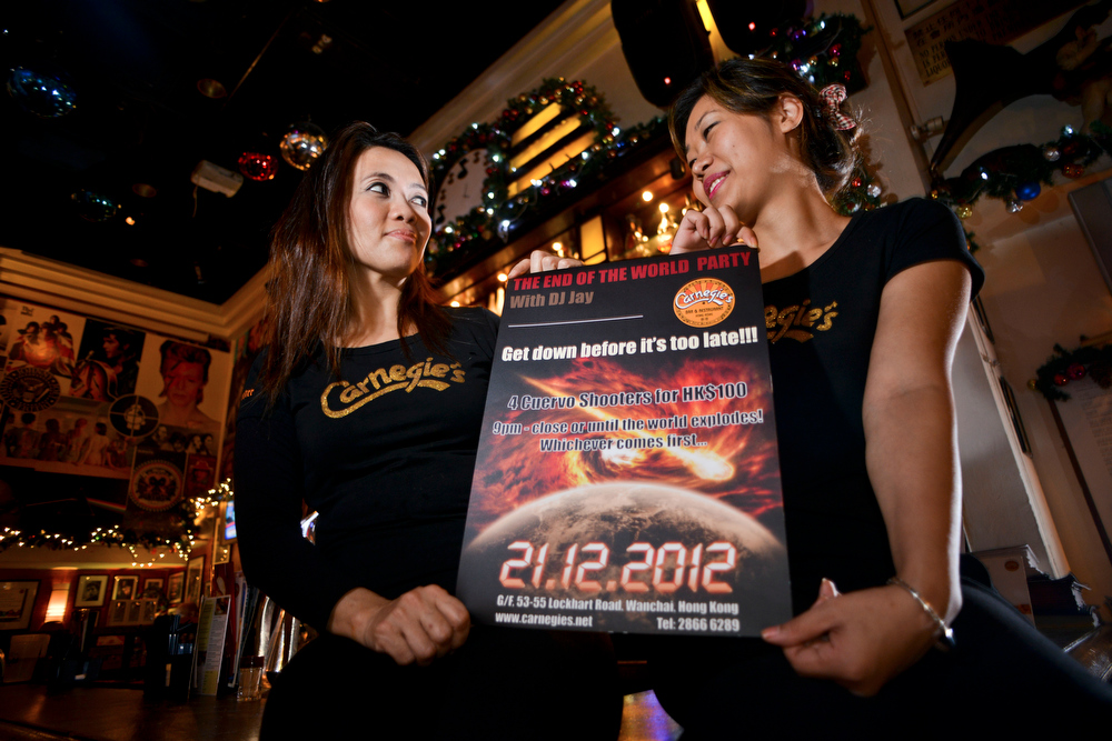 ". Yashen (R) and Neetu, staff of the bar Carnegie\'s, pose as they hold a flyer for the ""end of the world\' party, in Hong kong on December 21, 2012. Doomsayers hunkered down to await the coming apocalypse on December 21, but most took a lighthearted view of a Mayan \""prophecy\"" of the world\'s destruction, laying on stunts and parties to while away the end. ANTONY DICKSON/AFP/Getty Images"