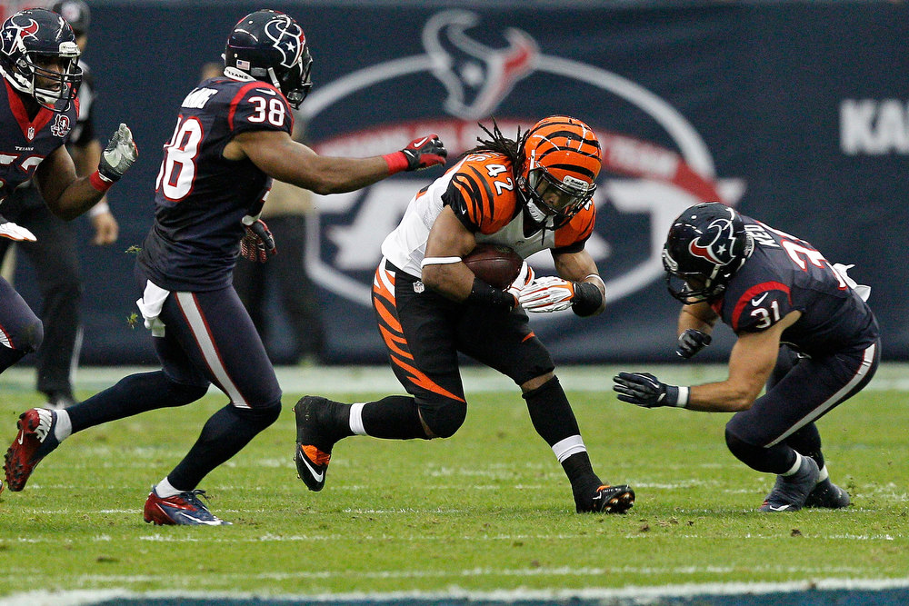 . BenJarvus Green-Ellis #42 of the Cincinnati Bengals runs the ball in the first half against Danieal Manning #38 and Shiloh Keo #31 of the Houston Texans during their AFC Wild Card Playoff Game at Reliant Stadium on January 5, 2013 in Houston, Texas.  (Photo by Bob Levey/Getty Images)