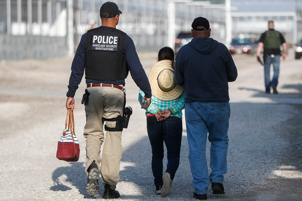 . Government agents take a woman suspected of living in the country illegally into custody during an immigration sting at Corso\'s Flower and Garden Center in Castalia, Ohio, Tuesday, June 5, 2018. The operation is one of the largest against employers in recent years on allegations of violating immigration laws. (AP Photo/John Minchillo)