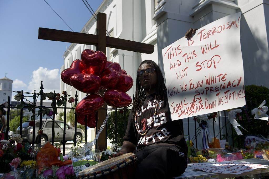 """. A man holds up a sign about white supremacy outside Emanuel AME Church on June 20, 2015 in Charleston, South Carolina.  A website apparently created by Dylann Roof emerged Saturday in which the accused Charleston church shooter rails against African Americans and appears in photographs with guns and burning the US flag. His arrest warrant revealed how on June 17 he allegedly shot the six women and three men, aged 26 through 87, multiple times with a high-caliber handgun and then stood over a survivor to make a \""""racially inflammatory\"""" statement.     AFP PHOTO/BRENDAN  SMIALOWSKI/AFP/Getty Images"""