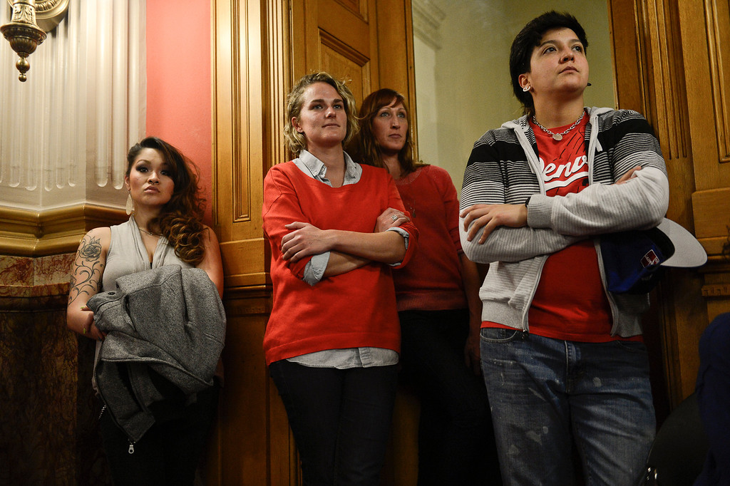 . Denver, CO. - January 23: Lauren Bernal 25 (left) and her partner Arielle Aragon 32 (right) listen to the Senate Judiciary Committee hear testimony on Senate Bill 11 with Jordan Beyer 27, and Melissa Van Goethem 36 (center) at the Denver State Capitol. Bernal and Aragon have been together for a year and would eventually take advantage of the bill passing to form a civil union.  Denver, Colorado January 23, 2013. (Photo By Joe Amon / The Denver Post)