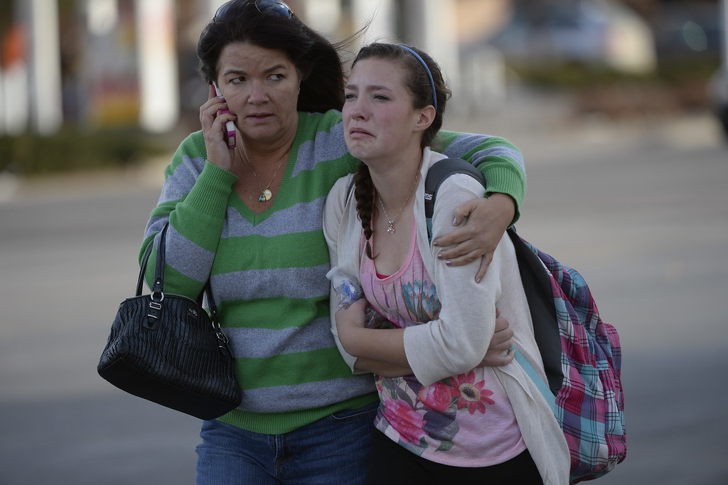 . CENTENNIAL, CO. - DECEMBER 13: Meredith Strecker comforts her daughter Madisen after being reunited outside Arapahoe High School in Centennial, CO December 13, 2013. Madisen is a freshman at the school where a student entered carrying a shotgun and asked where to find a specific teacher opened fire on Friday, wounding two fellow students before apparently killing himself, Arapahoe County Sheriff Grayson Robinson said. (Photo By Craig F. Walker / The Denver Post)