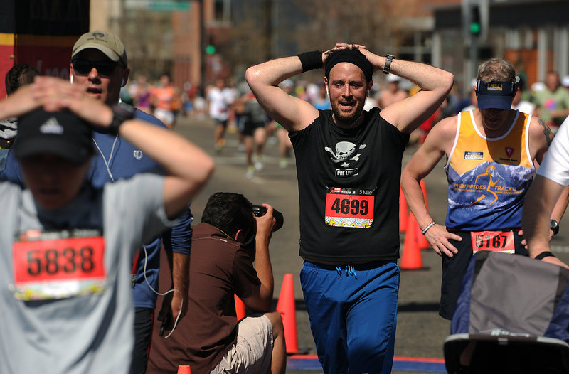 . Runners cross the finish line of the 5 mile race with their hands on their heads trying to cool off from the heat.  The 31st annual Cherry Creek Sneak had all sorts of distances for this year\'s race.  The Sneak, as it is affectionately named, had a 10 mile, 5 mile, 3.1 mile or 5K, a 1.5 mile Denver\'s 7 Sprint, and a kid\'s fun run for thousands of competitors, runners and walkers that turned out in the Cherry Creek neighborhood of Denver, CO on April 28, 2013.  The race is always held the last Sunday in April. This year participants cheered the national anthem and observed a moment of silence for victims of the Boston Marathon bombing at the start of each race. (Photo by Helen H. Richardson/The Denver Post)
