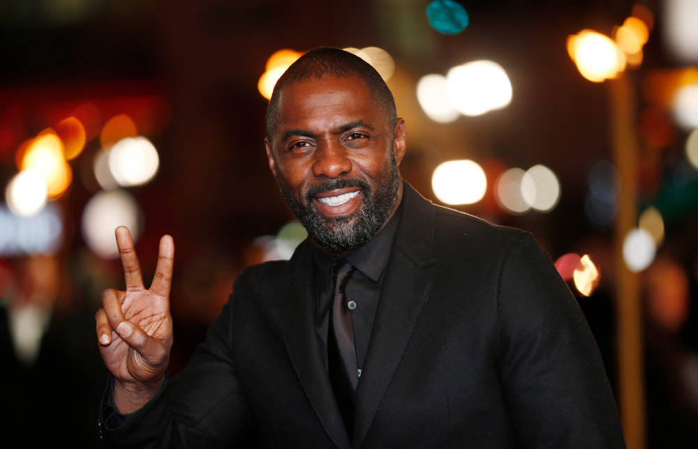 Description of . Actor Idris Elba gestures as he arrives for the world premiere of