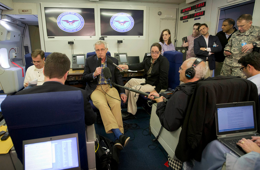 . U.S. Defense Secretary Chuck Hagel, center, is seen aboard a U.S. Military Aircraft before speaking to members of the media during his flight, Sunday, June 1, 2014. Hagel spoke about the released of U.S. Army Sgt. Bowe Bergdahl who was held hostage in Afghanistan, and who was handed over Saturday morning by members of the Taliban in exchange for five Afghan detainees held at the military prison in Guantanamo Bay prison in Cuba. (AP Photo/Pablo Martinez Monsivais, Pool)