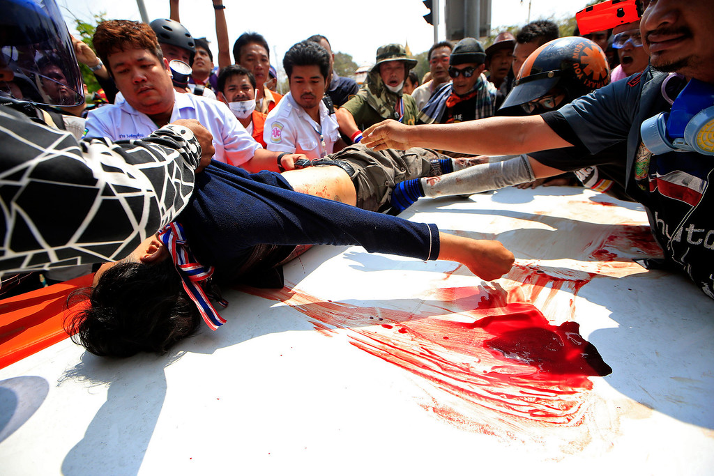 . An injured protester is helped by medic team to an ambulance during a clash between police force and anti-government protesters Tuesday, Feb. 18, 2014 in Bangkok, Thailand.  (AP Photo/Wason Wanichakorn)