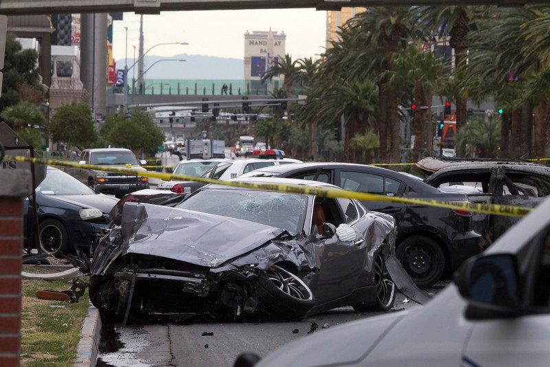 . Police rope off the scene of  a shooting and multi-car accident on the Las Vegas Strip in Las Vegas early Thursday, Feb. 21, 2013.  Authorities say at least one person in a Range Rover shot at people in a Maserati that then crashed into a taxi cab. The taxi cab burst into flames, and the driver and passenger were killed. The male driver of the Maserati also died, and his passenger was shot. (AP Photo/Las Vegas Sun, Steve Marcus)