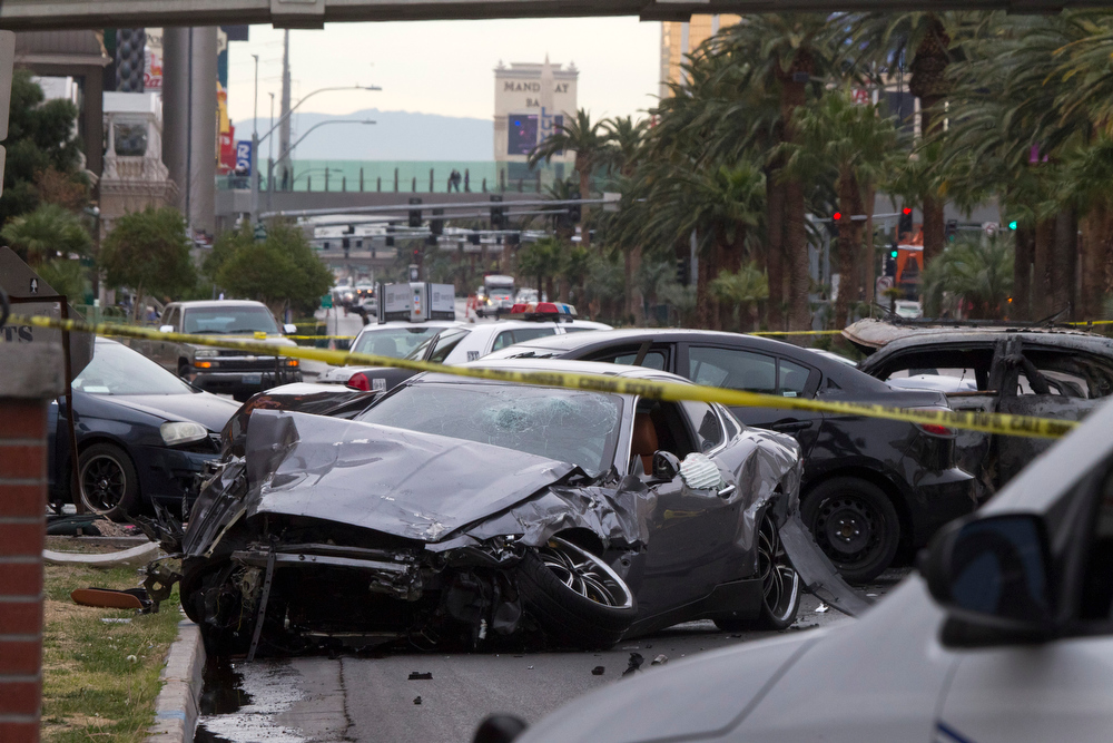 Description of . Police rope off the scene of  a shooting and multi-car accident on the Las Vegas Strip in Las Vegas early Thursday, Feb. 21, 2013.  Authorities say at least one person in a Range Rover shot at people in a Maserati that then crashed into a taxi cab. The taxi cab burst into flames, and the driver and passenger were killed. The male driver of the Maserati also died, and his passenger was shot. (AP Photo/Las Vegas Sun, Steve Marcus)