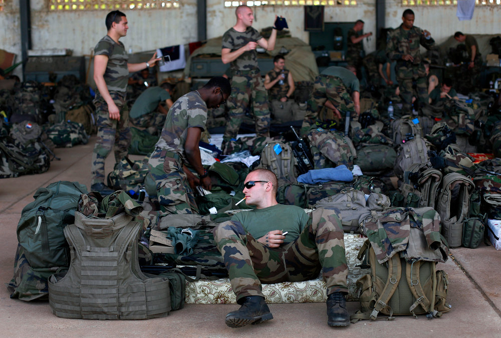 Description of . French troops gather in a hangar at Bamako's airport Tuesday  Jan. 15,  2013.  French forces led an all-night aerial bombing campaign Tuesday to wrest control of a small Malian town from armed Islamist extremists who seized the area, including its strategic military camp. A a convoy of 40 to 50 trucks carrying French troops crossed into Mali from Ivory Coast as France prepares for a possible land assault. Several thousand soldiers from the nations neighboring Mali are also expected to begin arriving in coming days. (AP Photo/Jerome Delay)