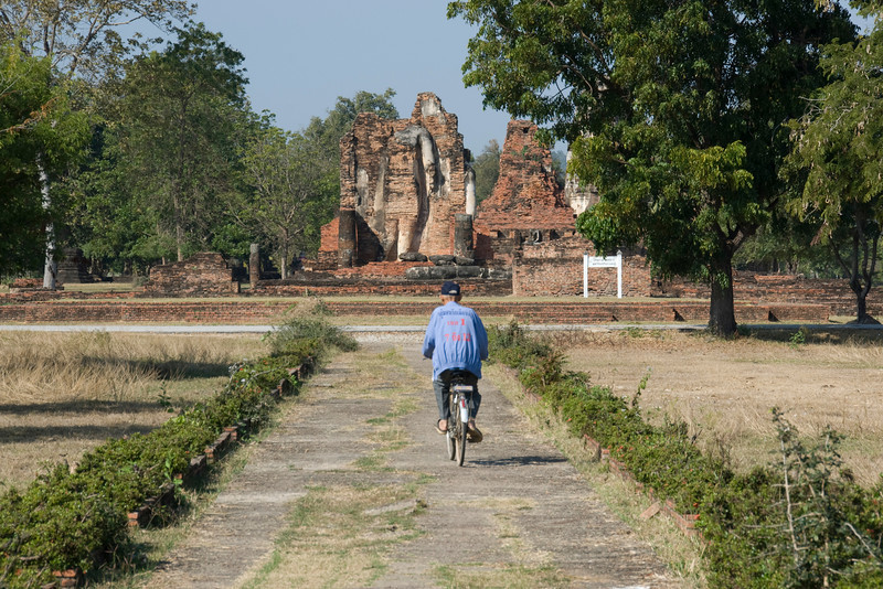 Man on bike inside the Wat Mahathat complex - Sukhothai, Thailand