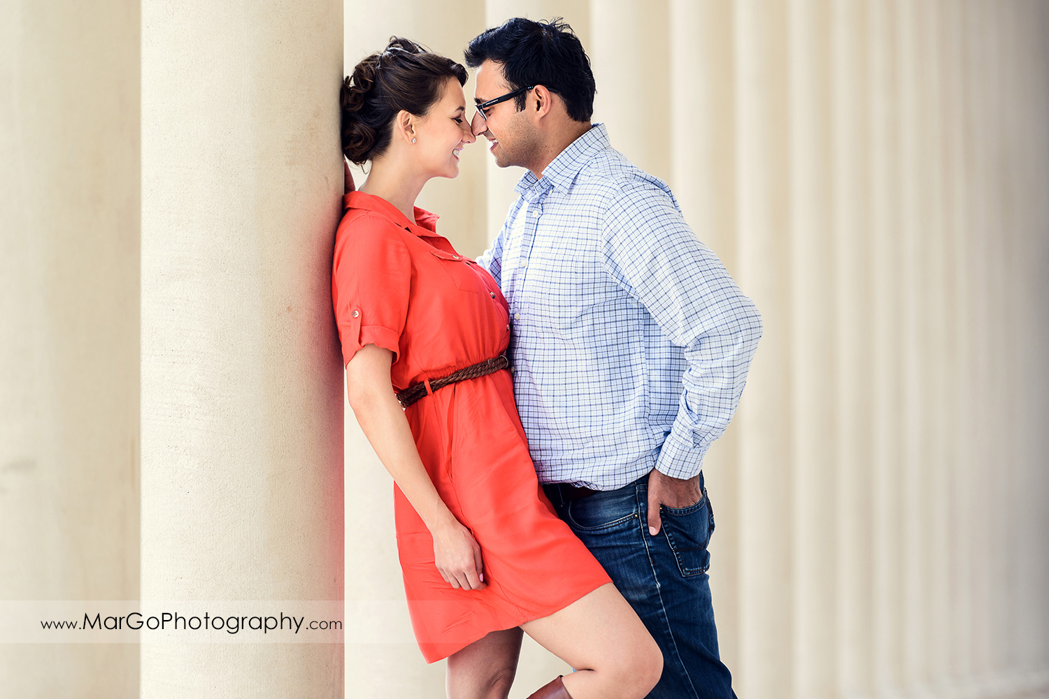 3/4 portrait of woman in red dress and man in blue shirt looking at each other with white columns background during engagement session at San Francisco Legion of Honor