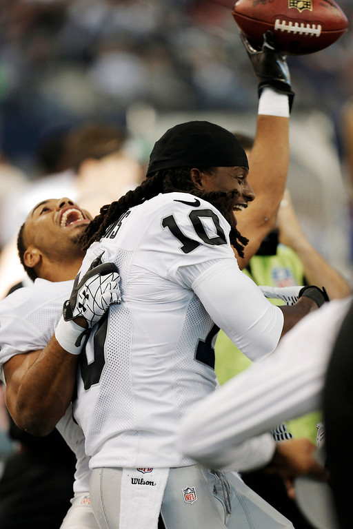 . Oakland Raiders wide receiver Greg Jenkins (10) celebrates his touchdown against the Dallas Cowboys with Rashad Jennings (27) during the first half of an NFL football game, Thursday, Nov. 28, 2013, in Arlington, Texas.  (AP Photo/Brandon Wade)