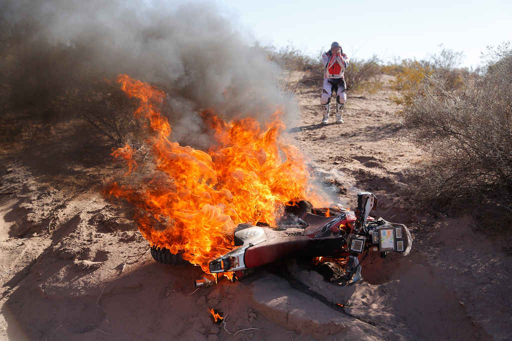 . Honda rider Paulo Goncalves of Portugal, right, reacts as he sees his motorcycle on fire during the fifth stage of the Dakar Rally between the cities of Chilecito and Tucuman in San Miguel de Tucuman, Argentina, Thursday, Jan. 9, 2014. (AP Photo/Victor R. Caivano, File)