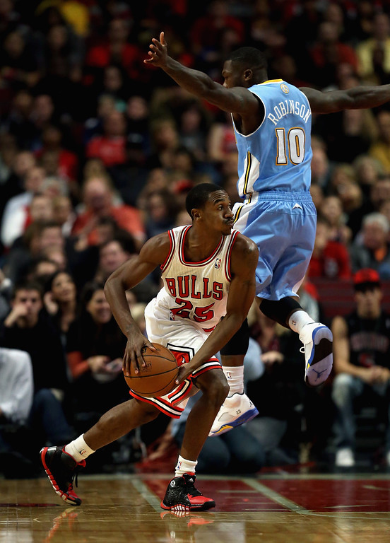 . Marquis Teague #25 of the Chicago Bulls moves to avoid Nate Robinson #10 of the Denver Nuggets during a preseason game at the United Center on October 25, 2013 in Chicago, Illinois. (Photo by Jonathan Daniel/Getty Images)