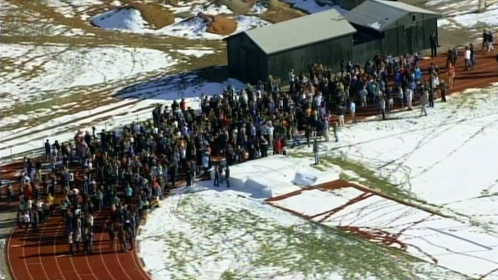 """. In this framegrab taken from video by KCNC television news in Denver, students of Arapahoe High School in Centennial, Colorado gather at a running track on December 13, 2013 after a shooting at the school. Two students were injured in the shooting incident before the suspected gunman apparently killed himself, the local sheriff said. The suspect was also a student. \""""That individual is .. deceased, he apparently killed himself,\"""" Arapahoe County Sheriff Grayson Robinson told reporters.     AFP PHOTO / KCNC /AFP/Getty Images"""