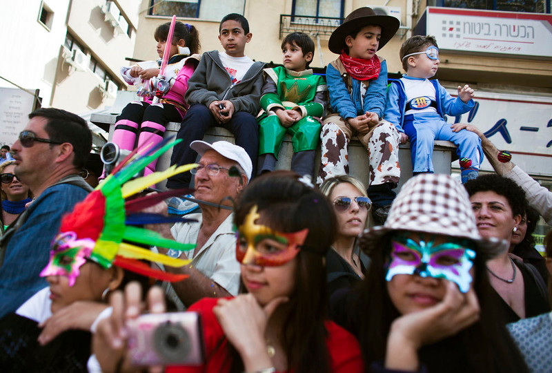 . People, some dressed in costumes, watch the annual parade for the Jewish holiday of Purim, in the Israeli city of Holon, near Tel Aviv February 24, 2013. Purim is a celebration of the Jews\' salvation from genocide in ancient Persia, as recounted in the Book of Esther. REUTERS/Nir Elias