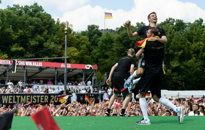 . Germany\'s goalkeeper Manuel Neuer (R) holds Germany\'s midfielder Thomas Mueller during celebrations for the German national football team at Berlin\'s landmark Brandenburg Gate on July 15, 2014, after they won the FIFA football World Cup 2014 in Brazil. The team comes to Berlin for a victory parade at landmark Brandenburg Gate to celebrate their fourth World Cup title, after their 1-0 win over Argentina on July 13, 2014 in Rio de Janeiro in the FIFA World Cup Brazil final game. (CLEMENS BILAN/AFP/Getty Images)
