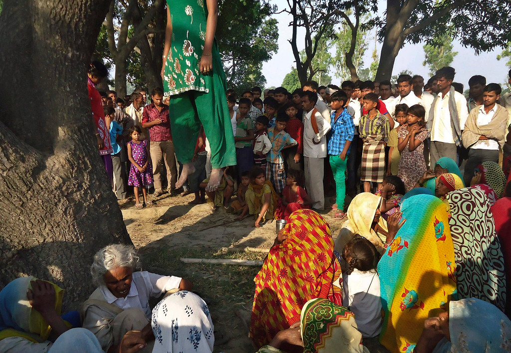 . In this Wednesday, May 28, 2014 photograph, Indian villagers gather around the bodies of two teenage sisters hanging from a tree in Katra village in Uttar Pradesh state, India. Two teenage sisters in rural India were raped and killed by attackers who hung their bodies from a mango tree, which became the scene of a silent protest by villagers angry about alleged police inaction in the case. Two of the four men arrested so far were police officers. (AP Photo/File)