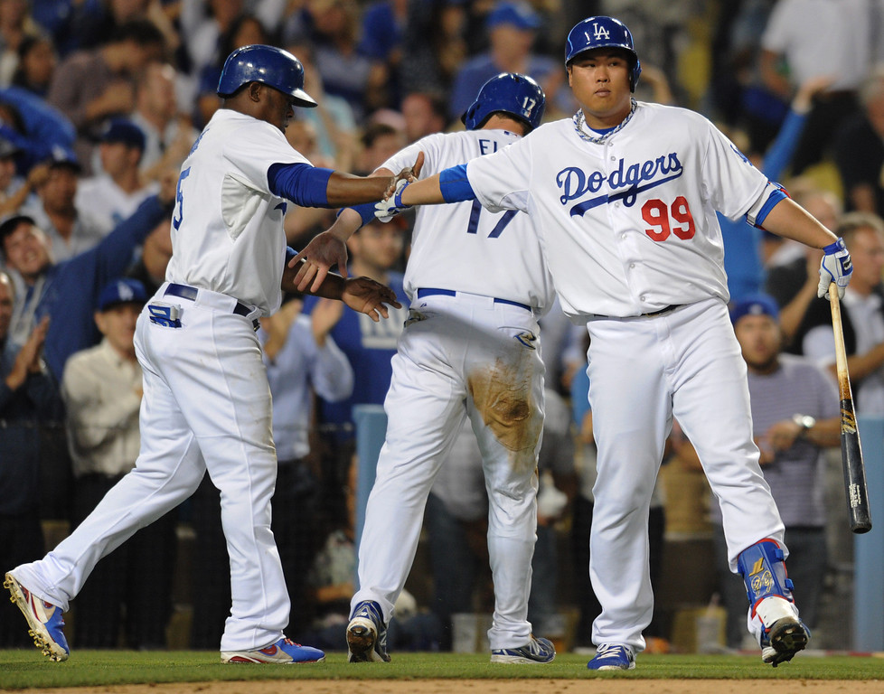 . Juan Uribe and A.J. Ellis are congratulated by Dodger Pitcher Hyun-Jin Ryu after being driven in by a Nick Punto double in the 5th inning. The Dodgers played the New York Mets in a game at Dodger Stadium in Los Angeles, CA. 8/13/2013(John McCoy/LA Daily News)