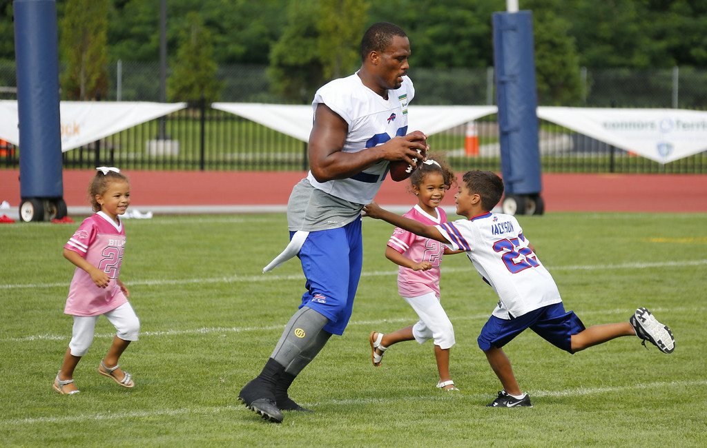 . Buffalo Bills running back Fred Jackson (22) plays with his children following a practice at their NFL football training camp in Pittsford, N.Y., Monday, July 21, 2014. With him are daughters Jaeden and Kaelen and son, Braeden (L-R). (AP Photo/Bill Wippert)