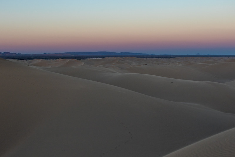 The Belt of Venus can be seen over distant mountains behind the Algodones Dunes in California after sunset