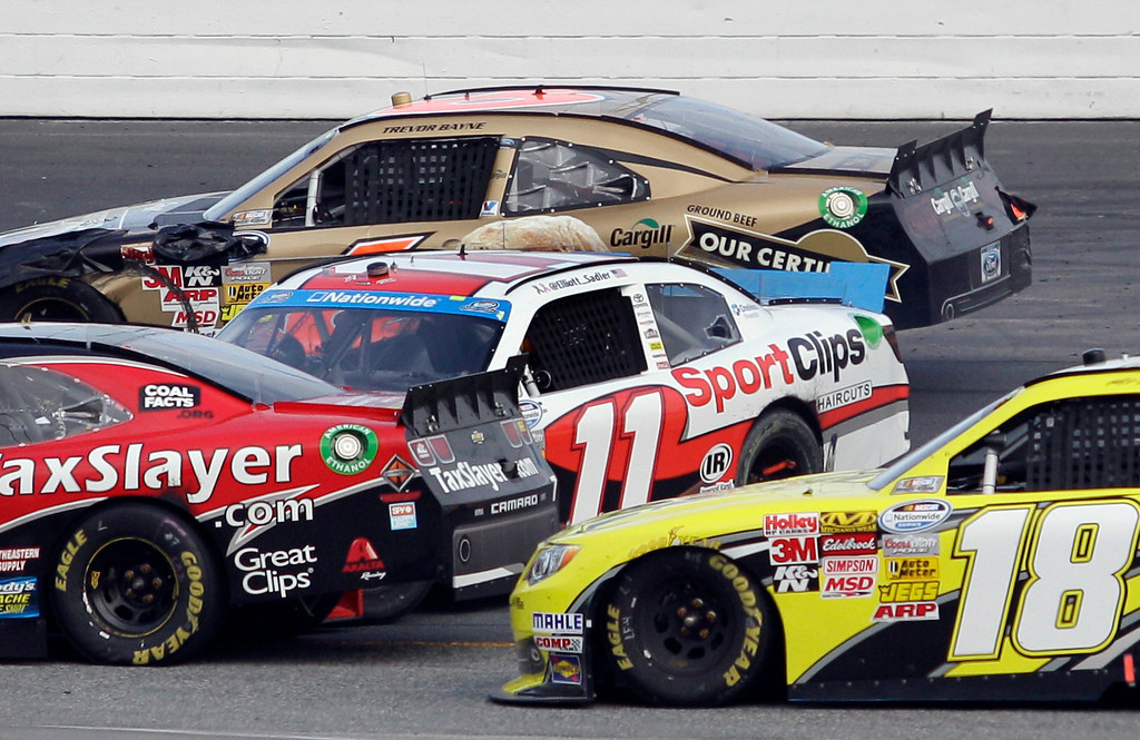 . Elliott Sadler (11) gets sideways as Regan Smith, left, Trevor Bayne, top, and Matt Kenseth (18) pass safely during the NASCAR Nationwide Series auto race, Saturday, July 13, 2013, at New Hampshire Motor Speedway in Loudon, N.H. (AP Photo/Mary Schwalm)
