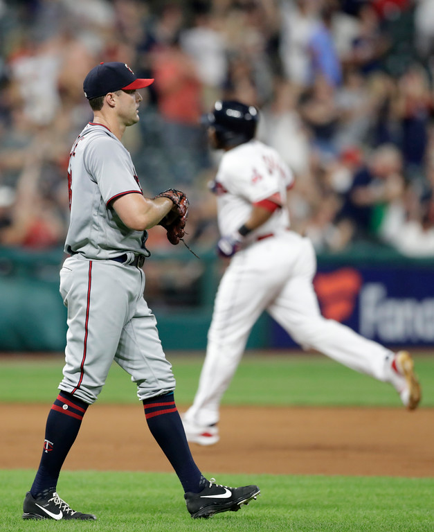 . Minnesota Twins\' Matt Belisle, left, waits for Cleveland Indians\' Edwin Encarnacion to run the bases after hitting a three-run home run in the seventh inning of a baseball game, Monday, Aug. 6, 2018, in Cleveland. (AP Photo/Tony Dejak)