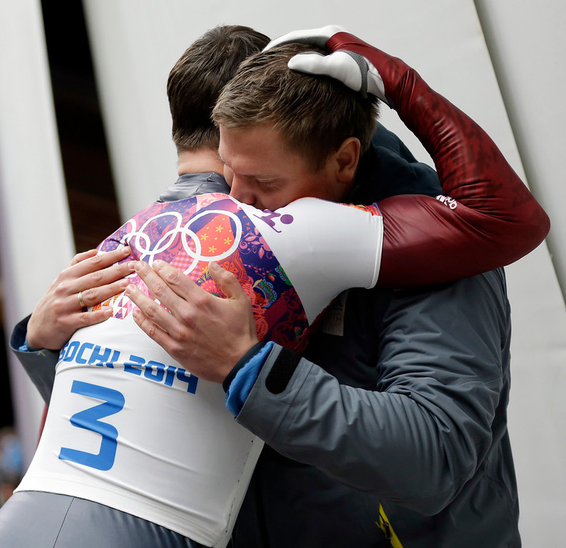 . Martins Dukurs of Latvia, left, is hugged by his brother Tomass Dukurs after Martins won the silver medal during the men\'s skeleton competition at the 2014 Winter Olympics, Saturday, Feb. 15, 2014, in Krasnaya Polyana, Russia. (AP Photo/Natacha Pisarenko)