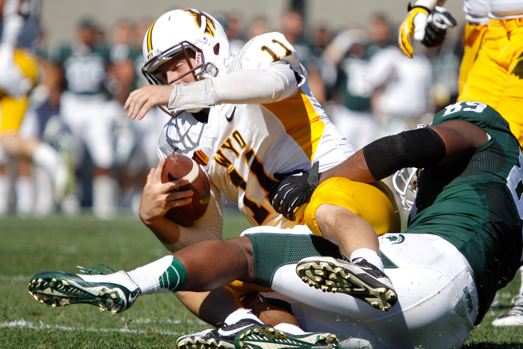 . Wyoming quarterback Colby Kirkegaard (11) is sacked by Michigan State\'s Shilique Calhoun during the first quarter of an NCAA college football game, Saturday, Sept. 27, 2014, in East Lansing, Mich. (AP Photo/Al Goldis)