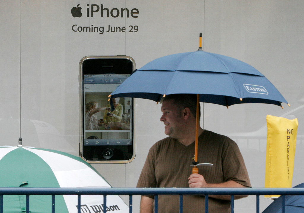 . An unidentified man waits under an umbrella in front of an Apple store while waiting for the release of the iPhone, Friday, June 29, 2007 in Columbus, Ohio. (AP Photo/Kiichiro Sato)