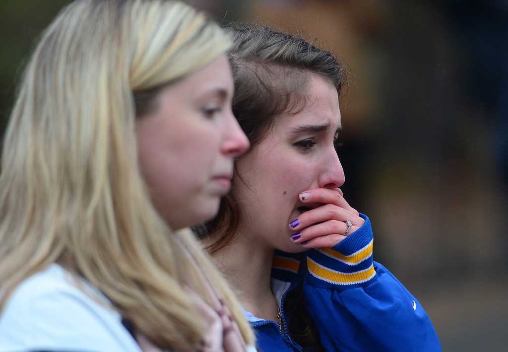 . Two teenagers grieve while paying their respects at a makeshift shrine to the victims of a elementary school shooting in Newtown, Connecticut, December 16, 2012.  A young gunman slaughtered 20 small children and six teachers on December 14,2012 after walking into a school in an idyllic Connecticut town wielding at least two sophisticated firearms.  EMMANUEL DUNAND/AFP/Getty Images