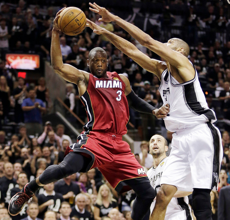 . Miami Heat\'s Dwyane Wade (3) is pressured by San Antonio Spurs\' Tim Duncan (21) during the second half of Game 3 in their NBA Finals basketball series, Tuesday, June 11, 2013, in San Antonio. (AP Photo/Eric Gay)
