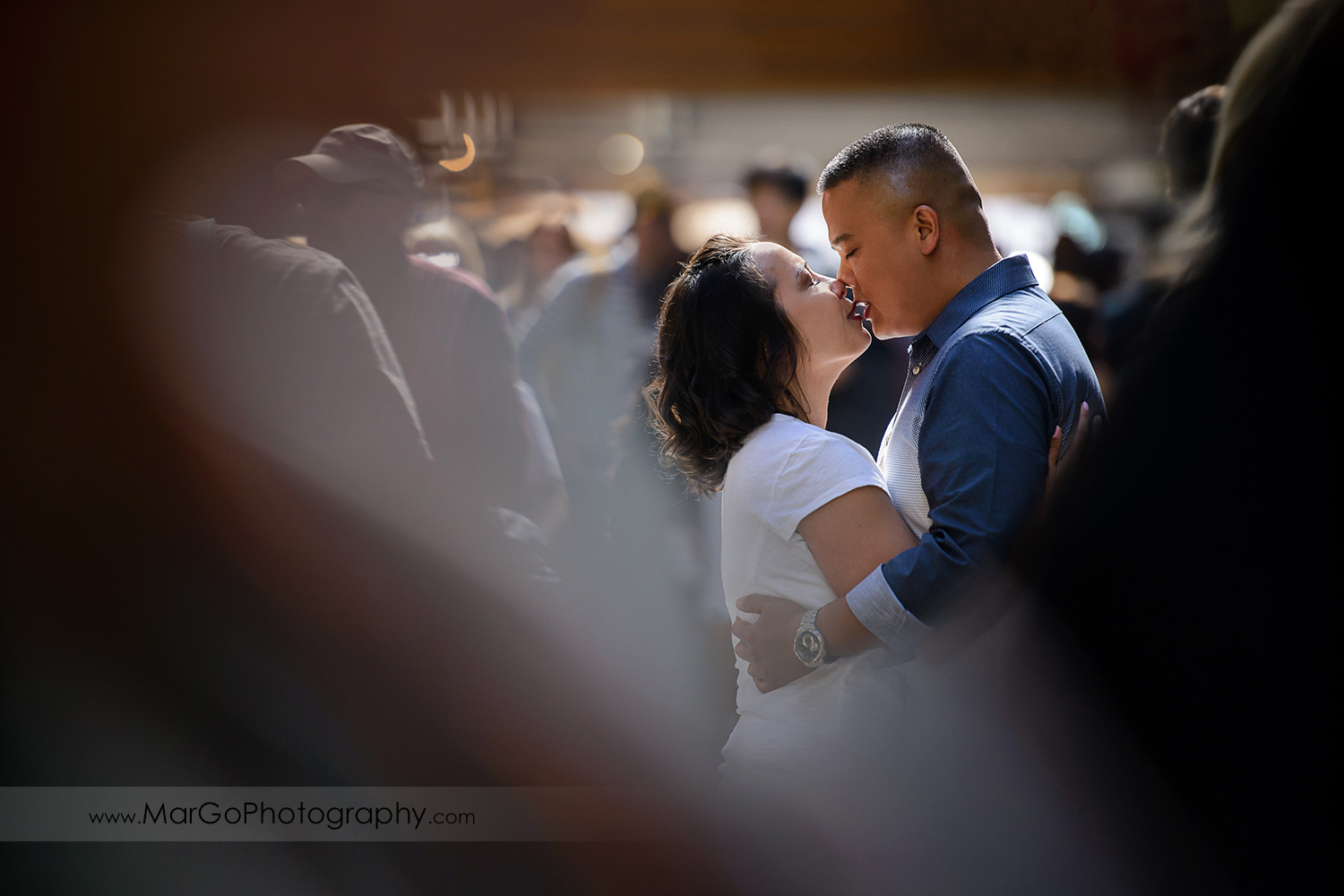 engagement session at Ferry Building in San Francisco - couple kissing in the crowd