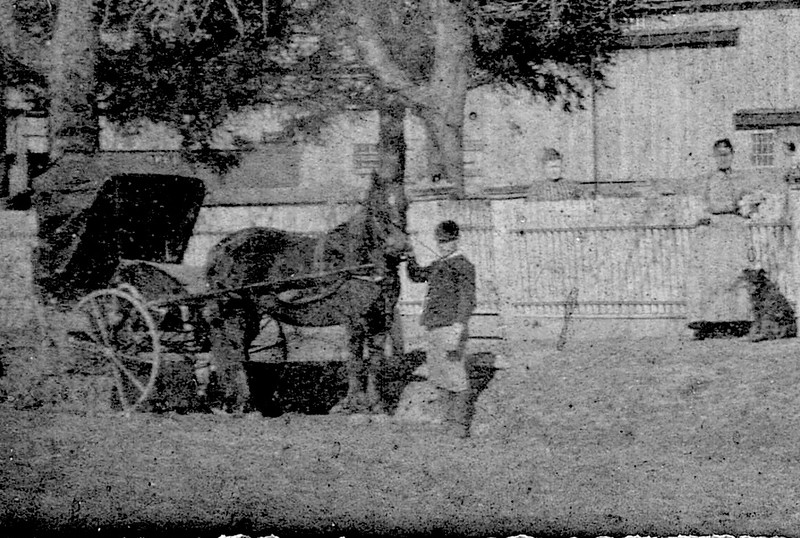 Abner Headley holds a horse in front of the house of Colonel Burnett on Elmood Ave.