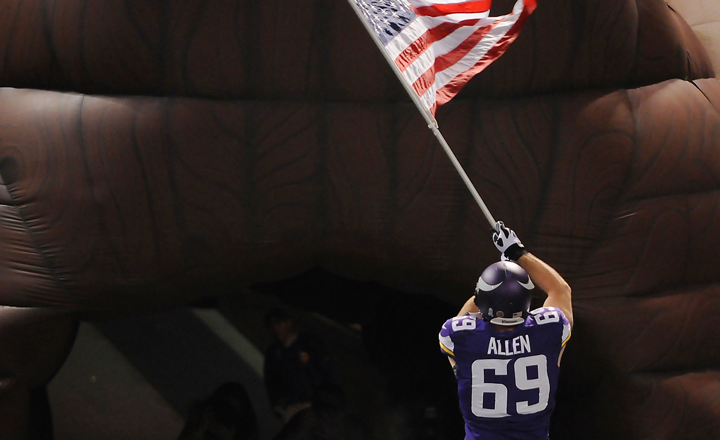 . Minnesota defensive end Jared Allen waves the American flag before the start of the game. (Pioneer Press: John Autey)