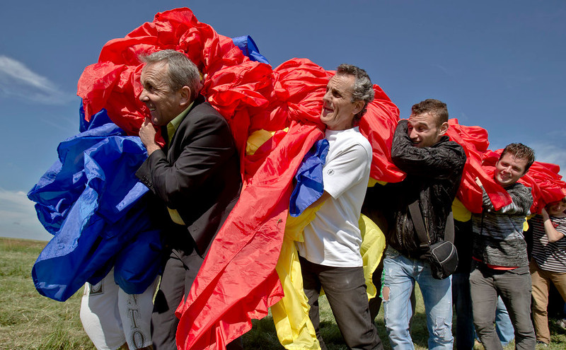 . Romanians carry a huge national flag on the Clinceni Airfield, south of Bucharest,  Romania, Monday, May 27, 2013. Romania entered the Guinness Book of records after it unveiled the largest flag ever made. It took about 200 people several hours Monday to unfurl a five-ton flag of Romania which organizers said measured 349.4 meters by 226.9 meters, about three times the size of a football pitch.(AP Photo/Vadim Ghirda)