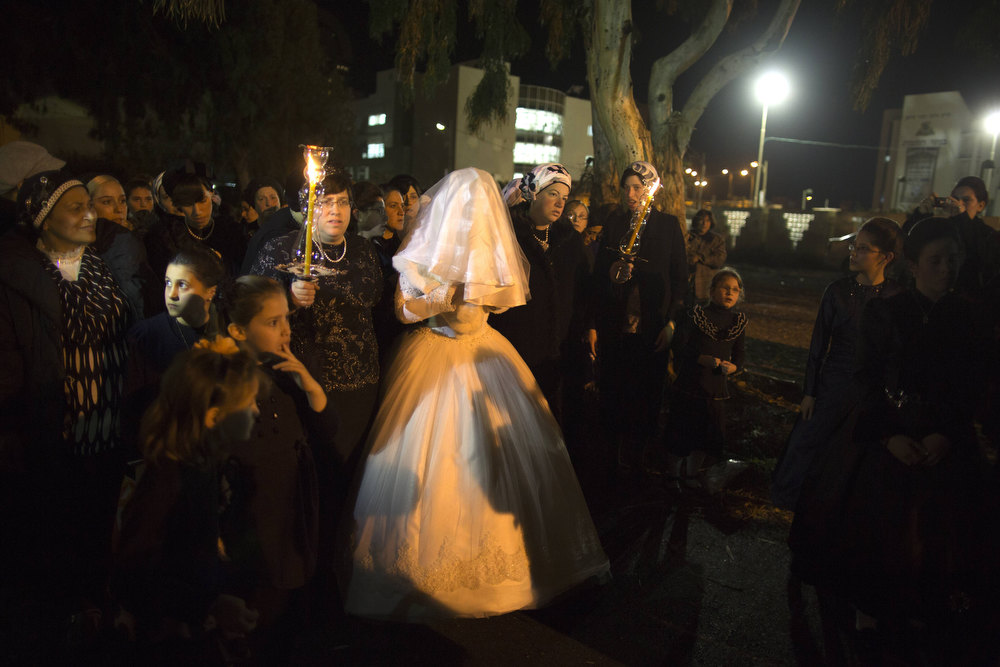 Description of . A Jewish bride arrives with family members during her wedding to the great-grandson of the Rabbi of the Tzanz Ultra-Orthodox Hasidic community in Netanya, on January 1, 2013. MENAHEM KAHANA/AFP/Getty Images